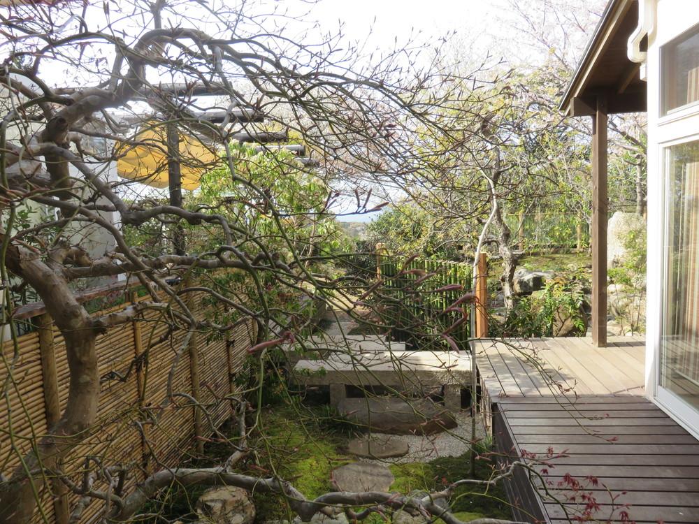 ベニシダレモミジの奥にはキッチンがあり、そこからは坪庭と石橋の先に海が見えます。