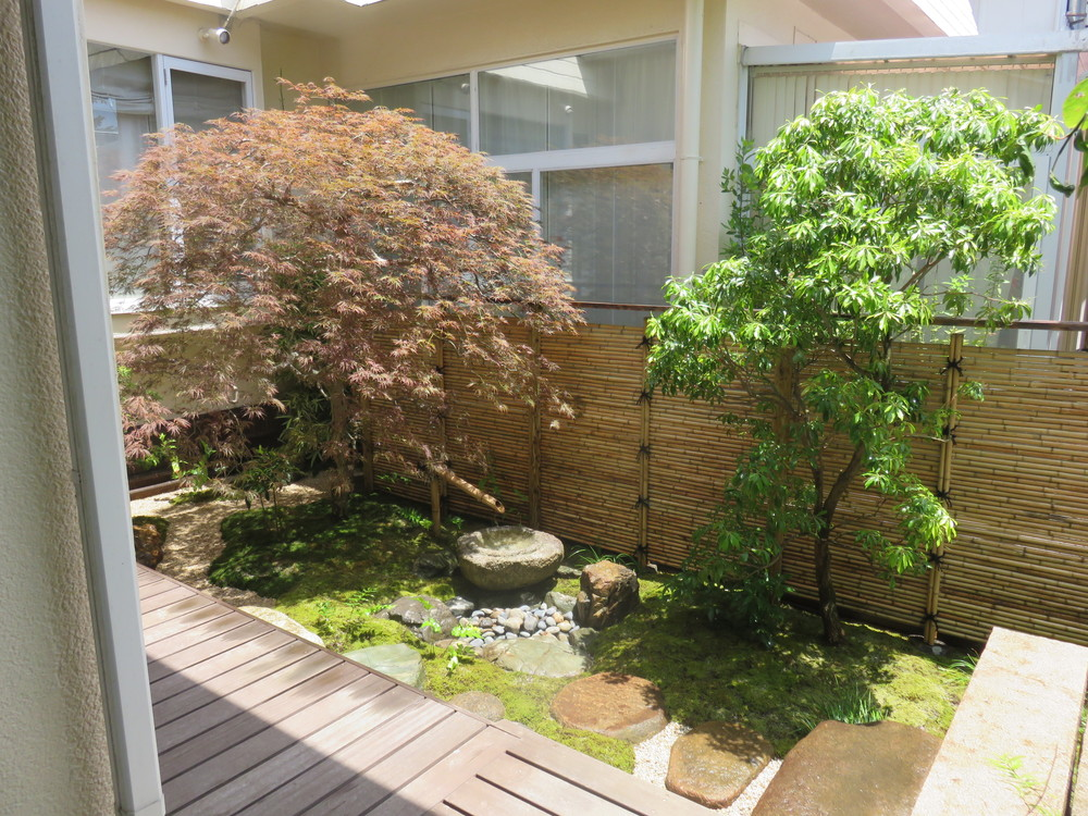 施工後です。洋間前から和室前まで続いていたウッドデッキを一部取り除き、石橋に架け替え、お庭に変化をつけました。