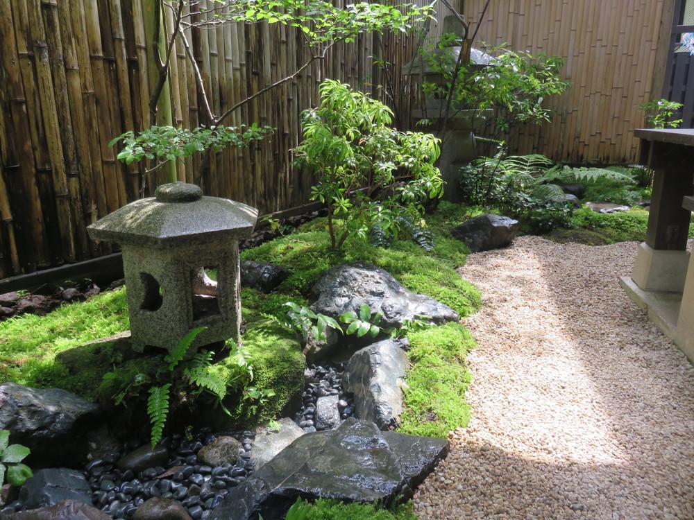 置き灯篭右下の石の間に水が流れ込んで行きます。奥には蹲踞も見えます。